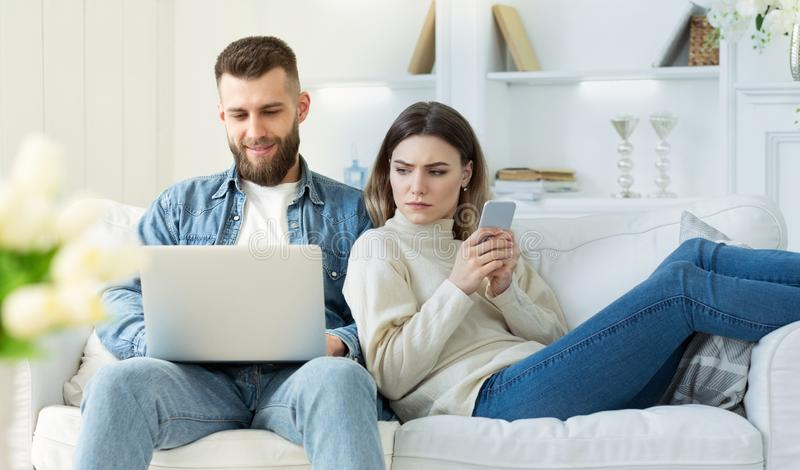 Distrust in relationships. Wife spying at man`s laptop. Sitting on sofa with cellphone in hands stock photo