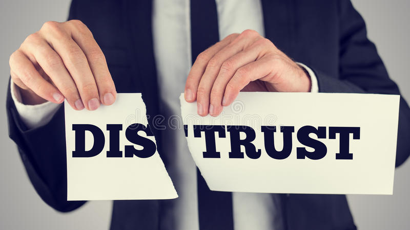 Distrust - trust. Businessman tearing up a sign saying - Distrust - conceptual image importance of trust and cooperation in successful business stock image