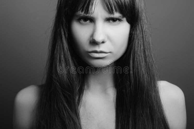 Distrustful insecure angry emotion girl portrait. Distrustful looking beautiful girl. Insecure facial expression. Black and white closeup portrait of emotional royalty free stock photo