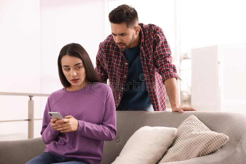Distrustful young man peering into girlfriend`s smartphone royalty free stock photos