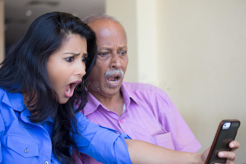 Disturbing news. Closeup portrait elderly gentleman in pink shirt and lady in blue top family shocked and at contents of mobile phone, indoors background stock images