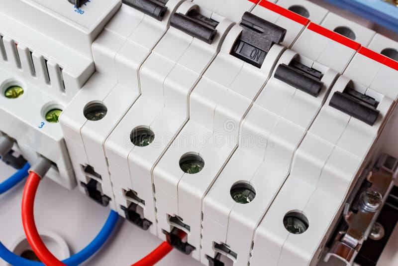 Disyuntores automáticos en el primer del carril del estruendo en la caja de montaje plástica blanca fotografía de archivo libre de regalías