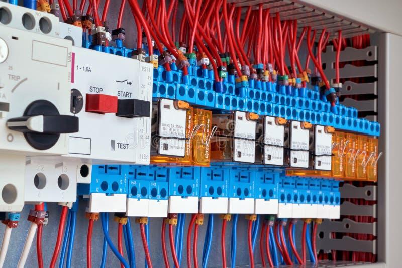 Disyuntores de la protección del motor y retransmisiones intermedias en gabinete eléctrico fotos de archivo