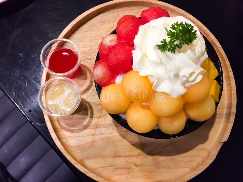 Dit is een mengelingsfruit Bingsu dat ijssneeuwvlokken is, met mango, kantaloep en watermeloen in een zwarte kop worden gecombine stock fotografie