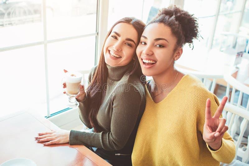 Dit is een selfie van twee mooie meisjes die tegelijkertijd zo verbazend en gelukkig kijken Zij zijn in koffie drinkend wat stock afbeelding