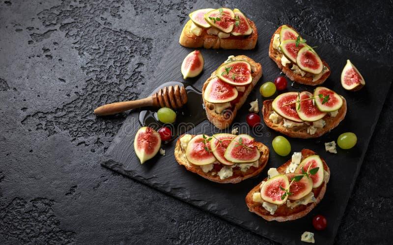 Dit Fig. en Gorgonzola-tartines, toost, bruschetta Gemotregend met honing royalty-vrije stock afbeelding