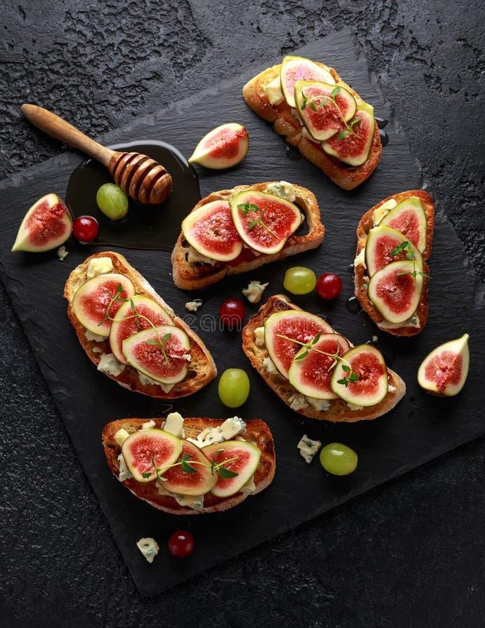 Dit Fig. en Gorgonzola-tartines, toost, bruschetta Gemotregend met honing stock afbeelding