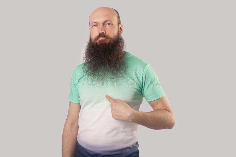 Dit is me! Portret die van de zekere midden oude kale mens met lange baard in lichtgroene t-shirt die, richten bevinden zich en royalty-vrije stock afbeelding