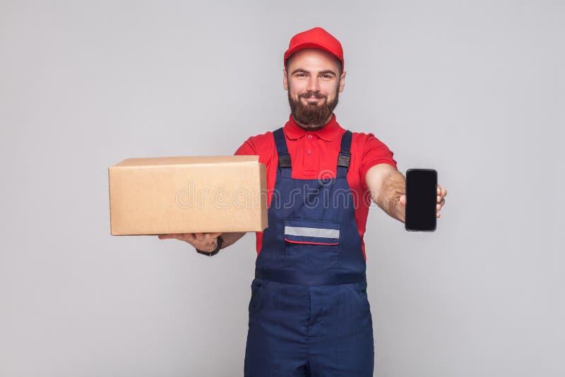 Dit is voor u! Jongelui die de logistische mens met baard in blauw u glimlachen royalty-vrije stock afbeelding