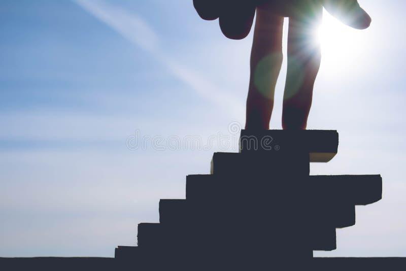 Dita che stanno alla cima delle scale verso la luce del sole, concetto fotografia stock