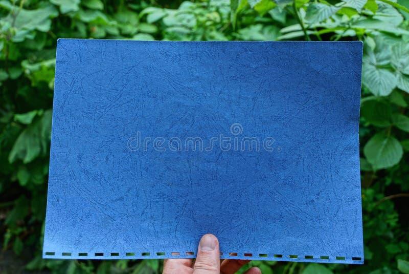 Dita che tengono strato di carta blu contro un fondo fotografia stock