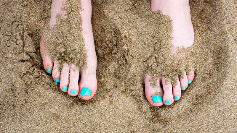 Dita del piede contro la sabbia alla spiaggia immagini stock libere da diritti