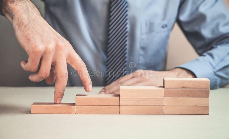 Dita dell'uomo che scalano sui blocchi di legno immagini stock