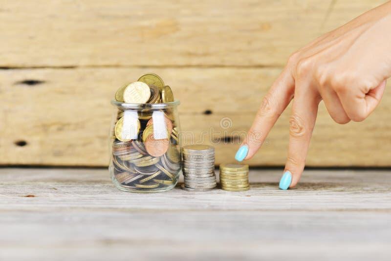 Dita di Woman's che scalano le scale di soldi ad un pieno del barattolo trasparente dei soldi, concetto finanziario di crescita immagine stock