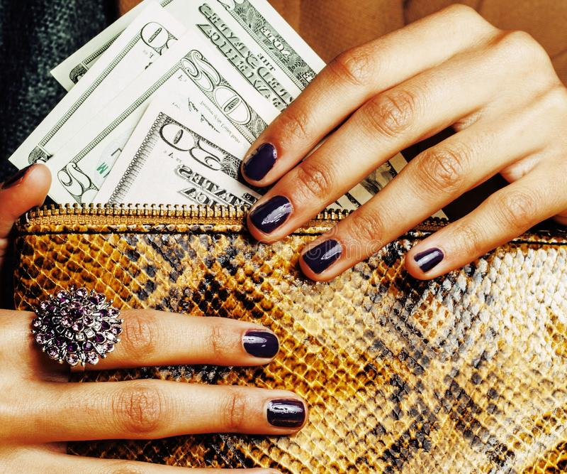 Dita graziose della fine afroamericana dei soldi della tenuta della donna su con la borsa, gioielli di lusso sulla frizione del p fotografia stock libera da diritti