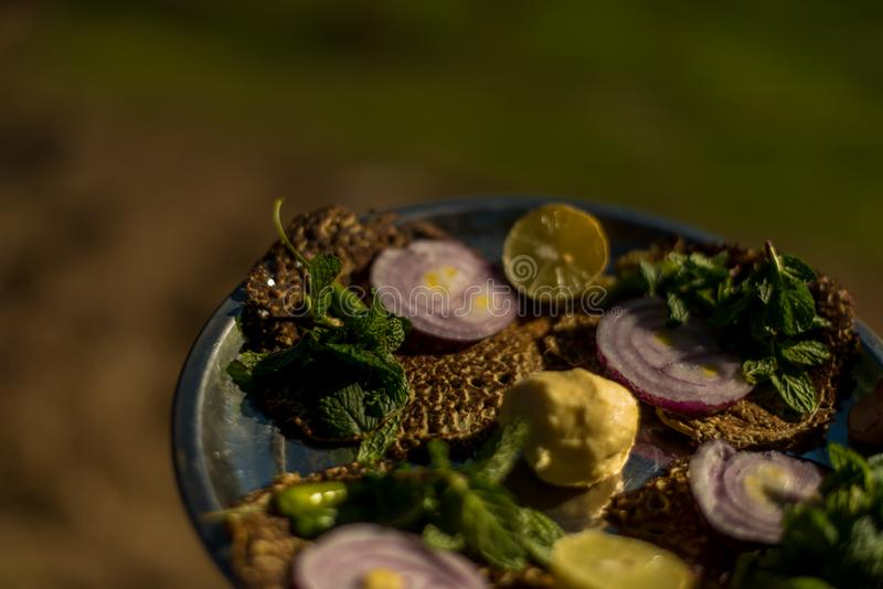 Dites l'arrosage et la nourriture du bout des l?vres authentique de Himachali au-dessus du fond blured de montagne images libres de droits