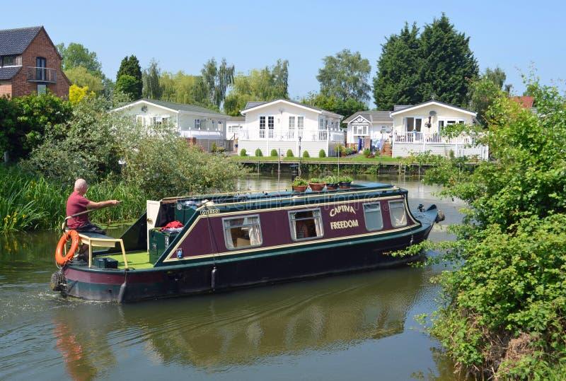 Ditional Zwęża się łódź na rzecznym Ouse z nadrzecznymi stróżówkami przy Buckden Marina Cambridgeshire fotografia royalty free