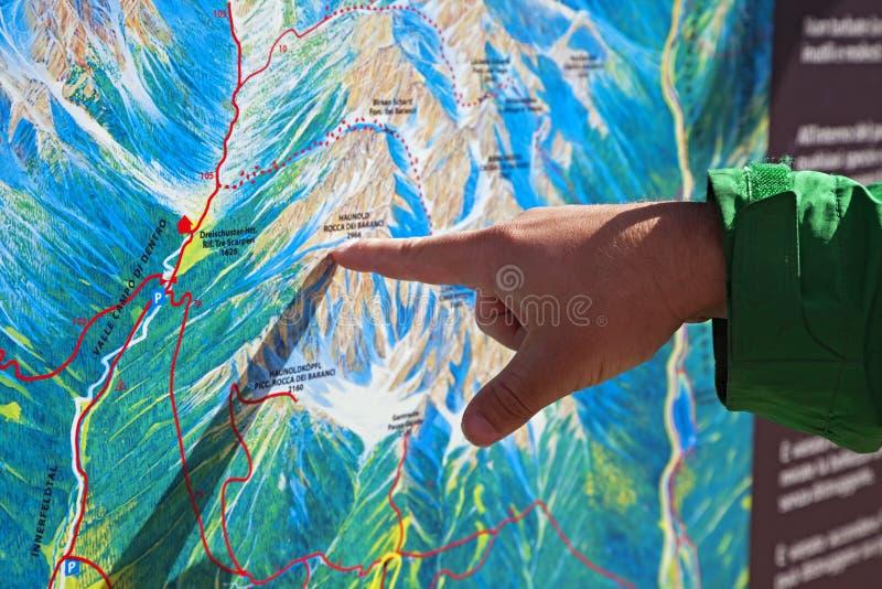 Dito che indica su una mappa di trekking fotografie stock