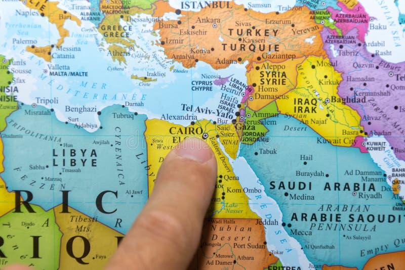 Dito che indica una mappa variopinta del paese dell'Egitto in Nord Africa in inglese e francese fotografia stock