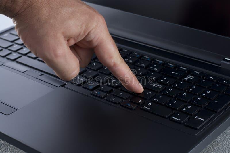 Dito che preme il tasto di introduzione su una tastiera del computer portatile immagine stock