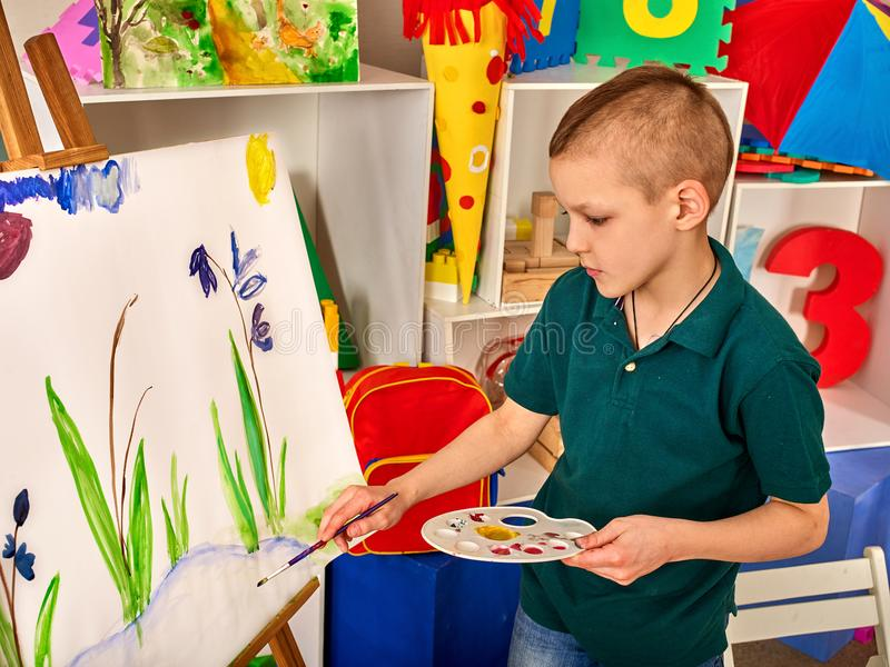 Dito della pittura del bambino sul cavalletto Il ragazzo del bambino impara la scuola della pittura fotografie stock libere da diritti