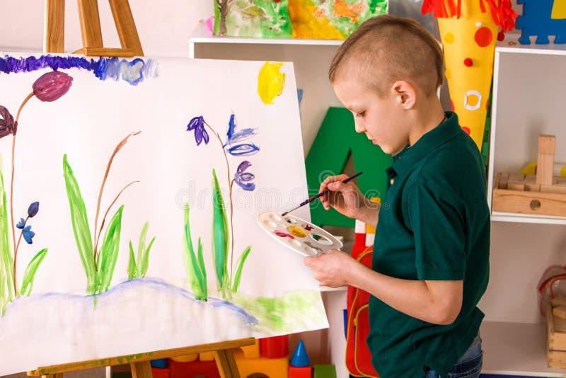 Dito della pittura del bambino sul cavalletto Il ragazzo del bambino impara la scuola della pittura immagine stock