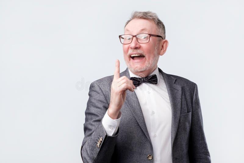 Dito indice di rappresentazione dell'uomo senior su, esprimendo parere fotografie stock