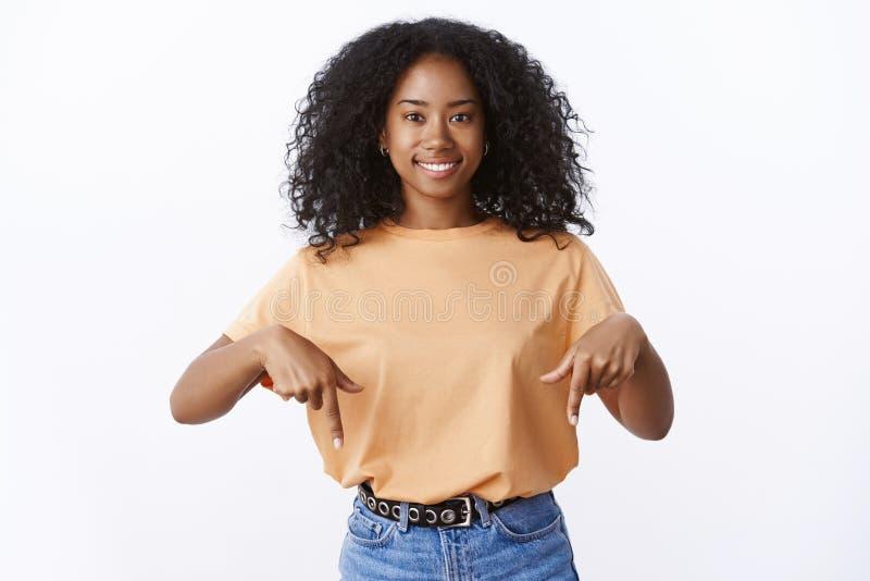Dito indice indicanti amichevoli sorridenti incantanti di giovane dell'afroamericano 20s della donna taglio di capelli vivace sve fotografia stock libera da diritti