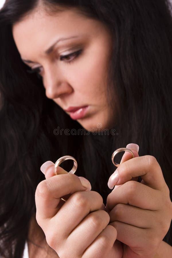 Divórcio. Anel de casamento triste do ouro da terra arrendada da mulher. imagem de stock royalty free