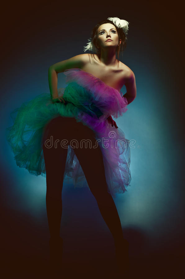 Diva. Glamorous girl in a gorgeous short dress with a feather in her hair, low key royalty free stock photography