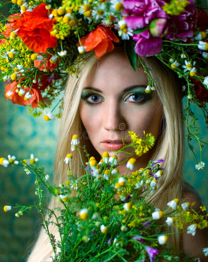 Diva. Beautiful blond woman with colorful flowers on her head royalty free stock photo