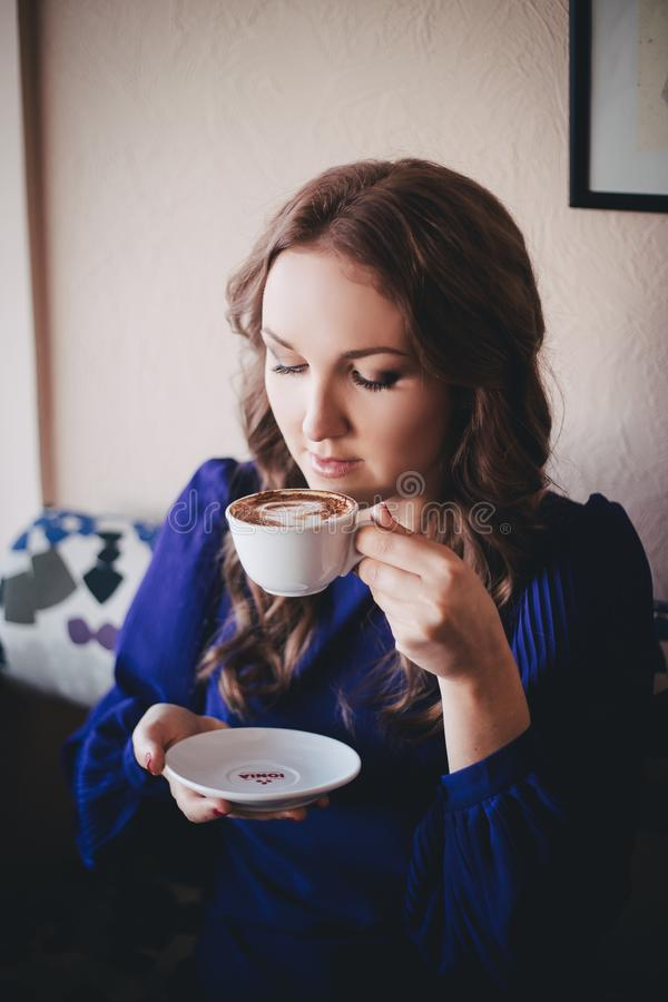 Diva angel mystic lady woman wearing casual blue dress lonely sitting in restaurant caffe with coffe cup awaiting her boyfreind hu. Sband in beautiful dreams stock photo