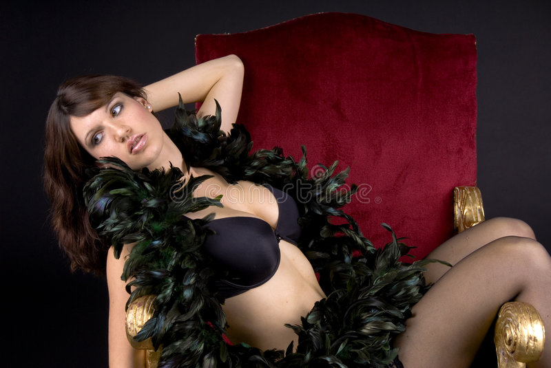 Diva In Black. Young brunette draped across a red velvet chair, wearing a black bra, and wrapped in a black feather boa stock photos