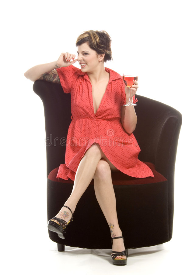 Diva with glass. Young attractive actress sits on a black velvet chair in a studio and sips on a glass of sangria royalty free stock photography