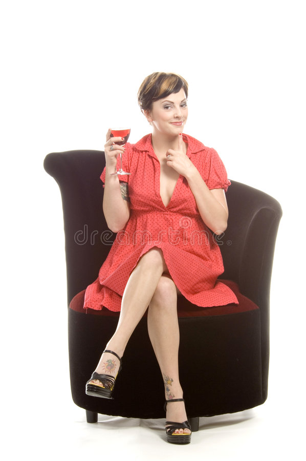 Diva with glass. Young attractive actress sits on a black velvet chair in a studio and sips on a glass of sangria stock image