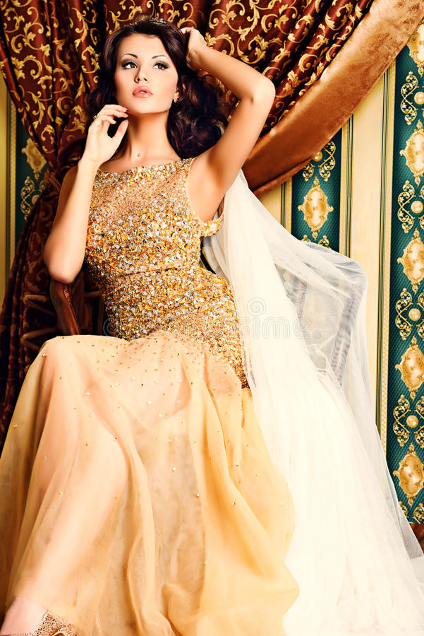 Diva woman. Fashion shot of a stunning woman in luxurious golden dress royalty free stock photography