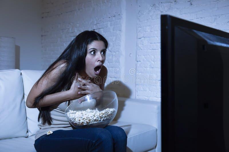 Divan latin de sofa de femme à la maison en film d'horreur de télévision de salon ou thriller effrayant de observation de suspens image libre de droits