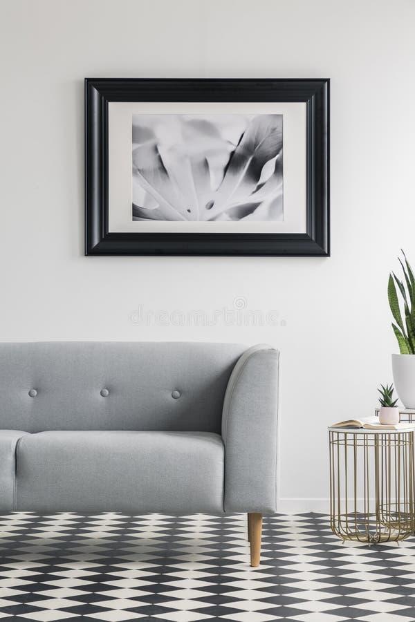 Divano grigio sul pavimento a quadretti nell'interno bianco del salone con la tavola ed il manifesto dell'oro Foto reale fotografie stock libere da diritti