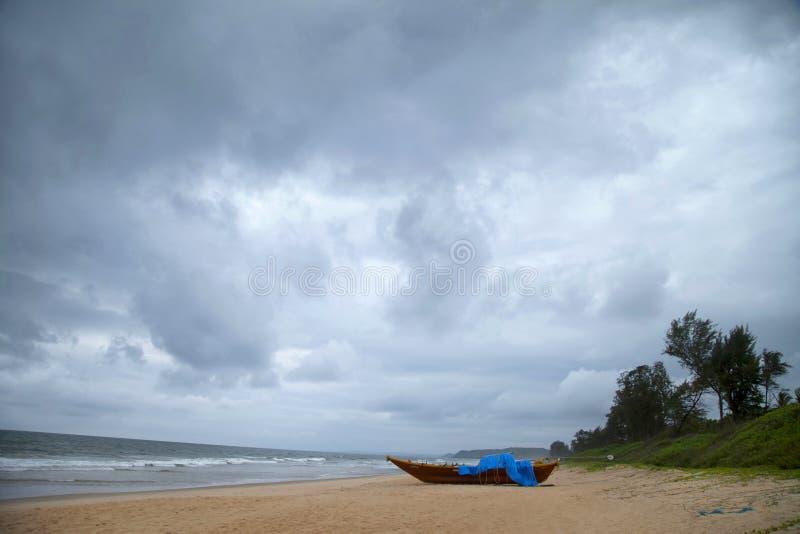 Diveagar strand med fartyget på en molnig dag arkivbilder