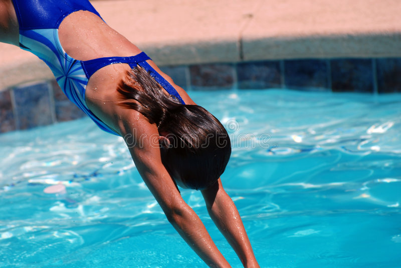 Diver. Little girl diving into a pool stock photo