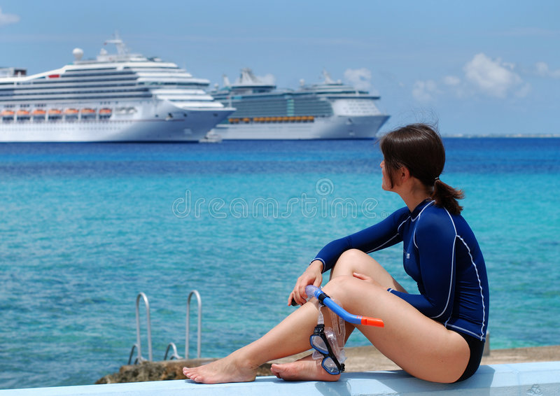 The Diver Girl. Watching at cruise liners anchored close to Grand Cayman island stock photos