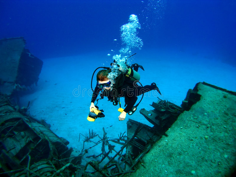 Diver photographing a Sunken Shipwreck. In Cayman Brac stock photo
