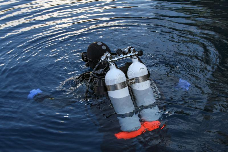 Diver plunges into the dark water deep lake royalty free stock photo