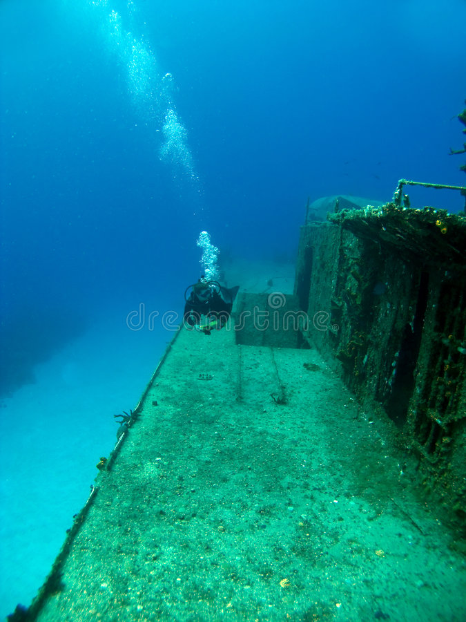 Diver swimming along side a Sunken Shipwreck. In Cayman Brac royalty free stock photos
