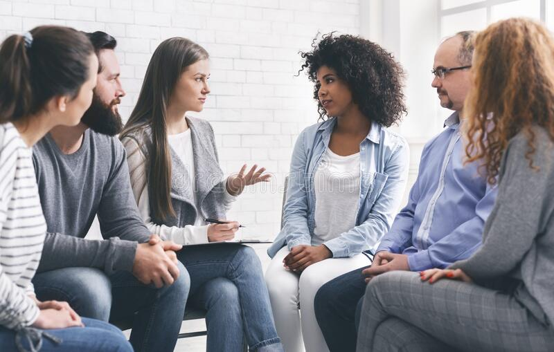 Diverce people talking with professional therapist at group meeting royalty free stock photo