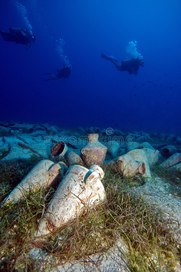 Divers and ancient amphoras. A groupd of scubadivers is diving at an ancient amphora area stock photography