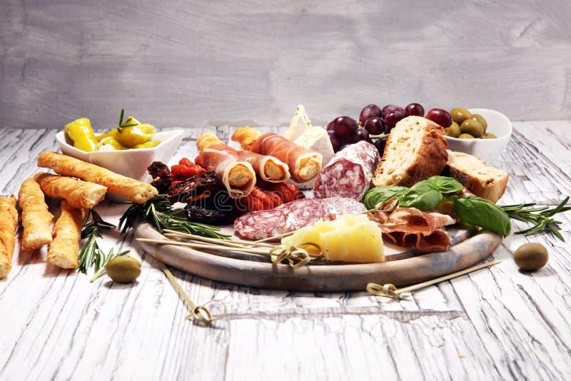 Divers ap?ritif d'Antipasto Planche ? d?couper avec le prosciutto, le salami, le fromage, le pain et les olives sur le fond en bo photo libre de droits