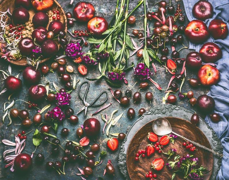 Divers baies et fruits d'été : fraises, pêches, prunes, cerises, groseilles à maquereau, groseilles sur la table de cuisine rusti photographie stock