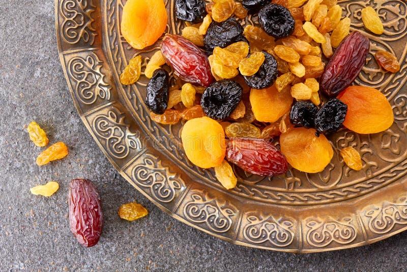 Divers fruits secs de plat toreutic au-dessus du fond en pierre photo libre de droits