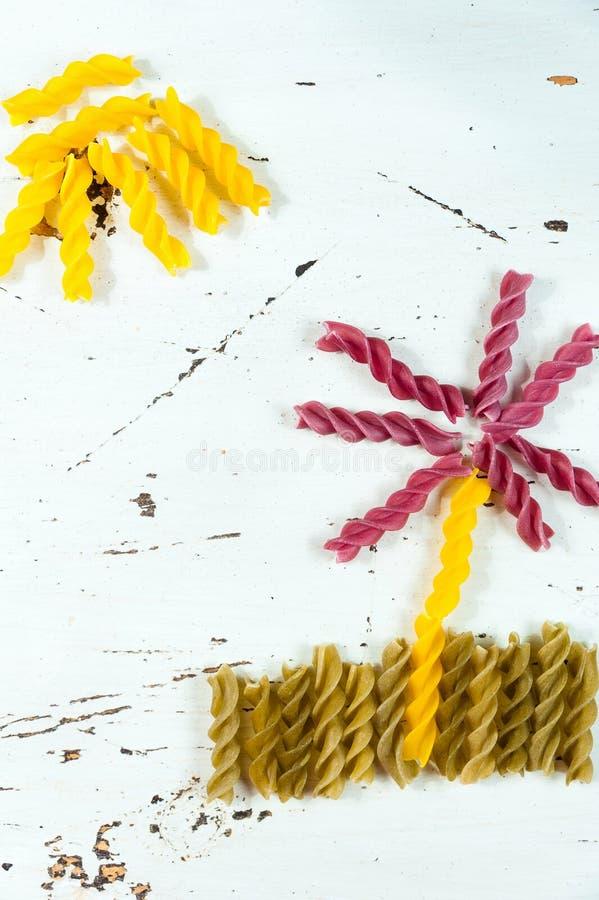 Divers genres de pâtes crues colorées sur un fond blanc, une vue supérieure, sous forme de gisements de fleur et de soleil de nou photo libre de droits